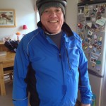 Roger Key Dressed in blue with a wolly hat and a bike helmet ready to go on a bike ride.